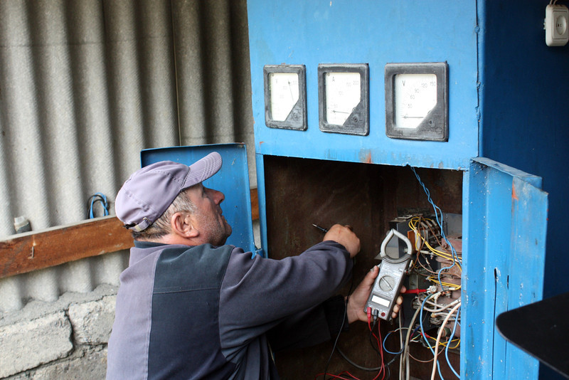 Ahshar Varziev checking the controls of his homemade hydro-power plant.