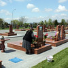 Grandmother arranging flowers at a grave in Beslan's City of Angels Cemetery.