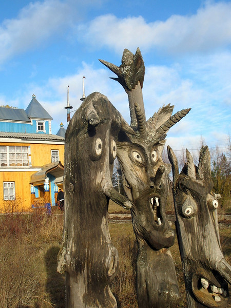Yegor Utrobin's sculptures with the home/museum he built in the background. (Perm Region, Russia)
