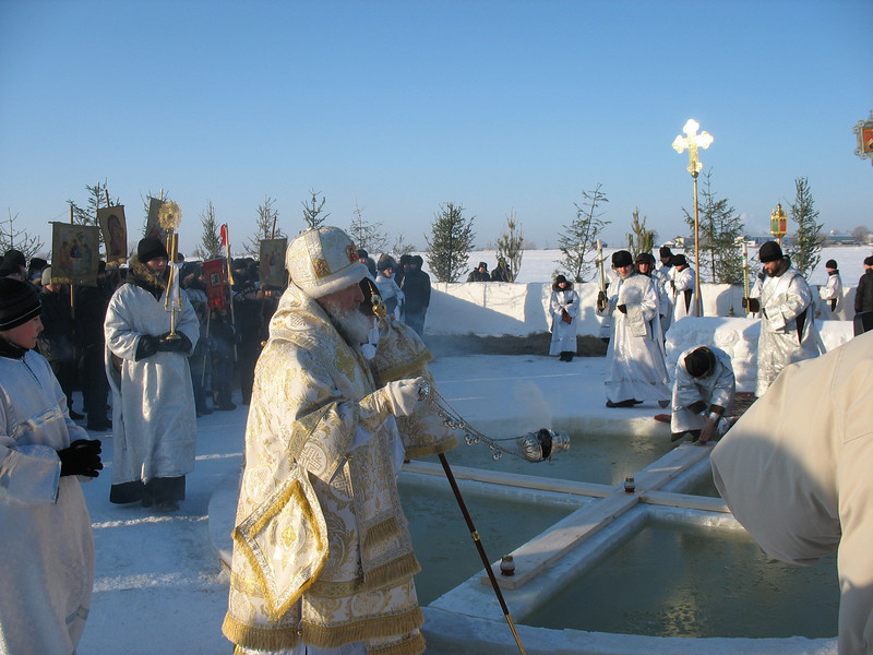Russian Orthodox priest sanctifying the Irtysh River in preparation or believers' baptisms.