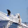 Shoveling snow off the roof on a sunny day.