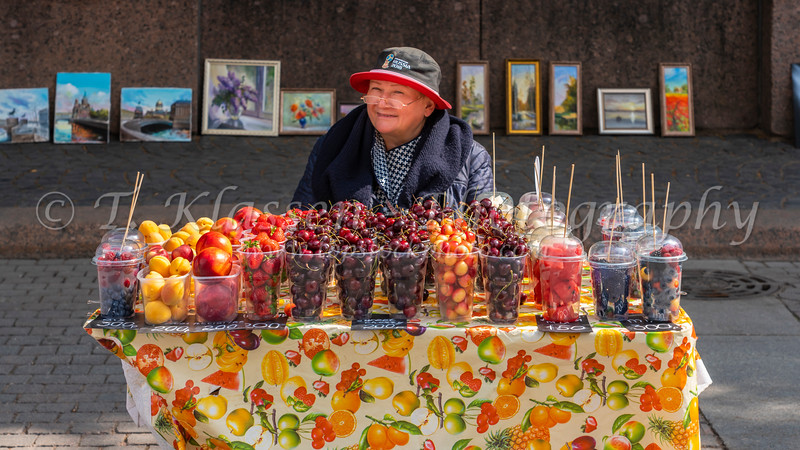 A freindly Russian lady selling fresh fruit at a kiosk on the street in St. Petersburg, Russia.
