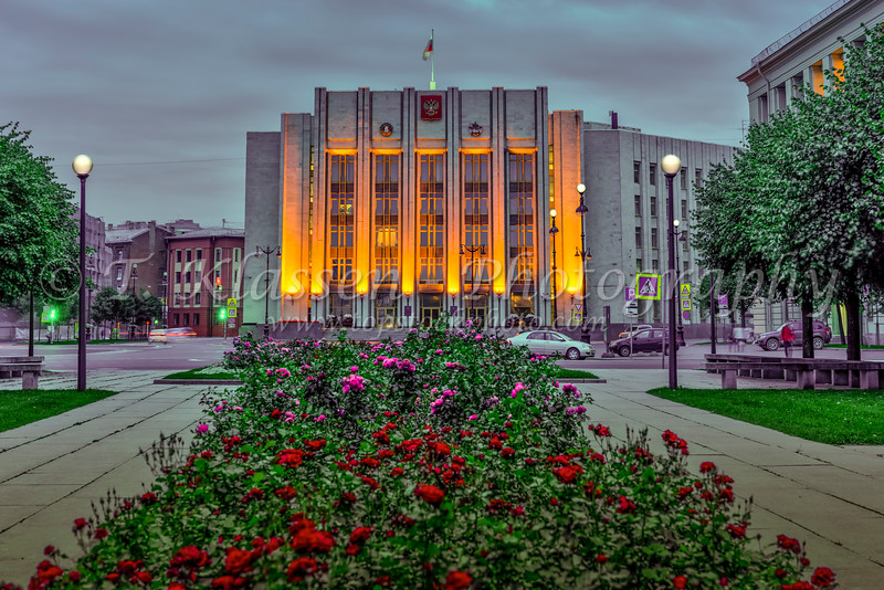 A government building illuminated at night and flowers in a park in St. Petersburg, Russia.