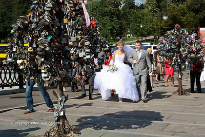 Metal trees of Love Padlocks or Love Locks, Luzhkov Bridge, Vodootvodny Canal, Moscow. A modern Russian Wedding Tradition. Bolotnaya Park and monument to Russian artist Ilya Repin in background.