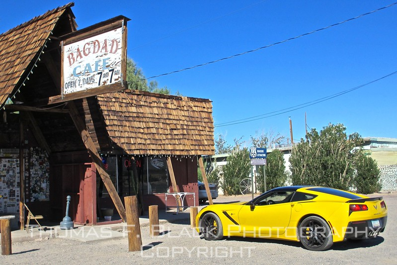"storied cafe on route 66 in newberry springs, ca. according to propriestress andrea pruett, it was featured in the 1987 german-produced film ""Bagdad cafe"" starring jack palance. it was not a box-office blockbuster. name of cafe , built in the 1950s, was changed in 1995. what caught my eye was the juxtaposition of the ramshackle building and the spanking-new corvette, in canary yellow, no less."