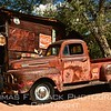 """1950s f-1, ford's original pickup series. pair of spares rest against building. big sign reads """"clabber girl baking powder. Praised by experts."""""""