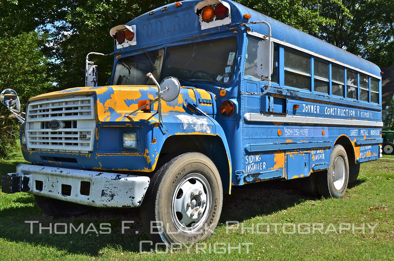 This and four frames following, retired school bus employed as roadside marquee for construction contractor in Dumas, AR, southeast of Pine Bluff. [UFP050311]