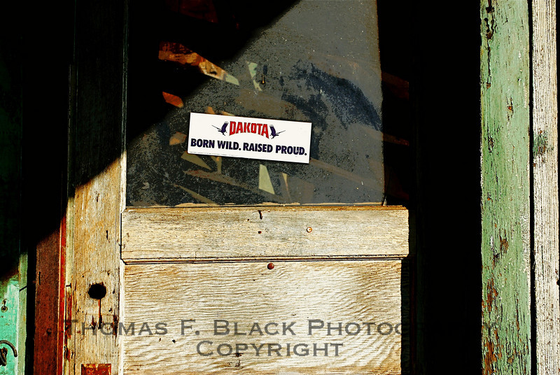 "Front door to abandoned shack, Hornitos, CA. Sign reads, ""DAKOTA. Born Wild. Raised Proud."" Dakota is a brand of ear corn.  [UFP 112908]"