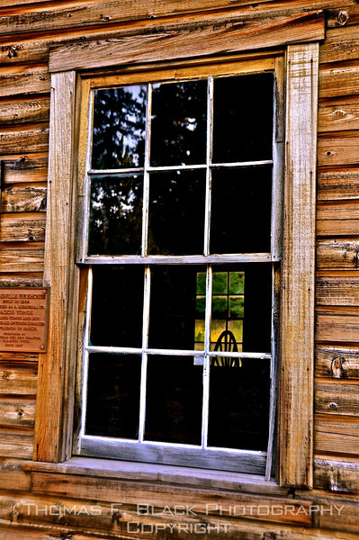 This frame and next, old wooden spinning wheel visible through window of abandoned barn, Plumas County, CA. [UFP080610]