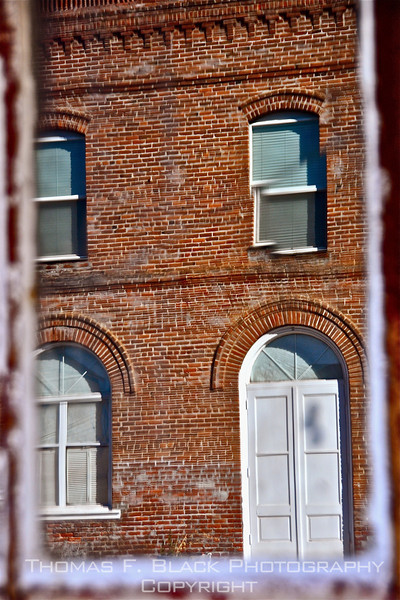 """Shaniko, OR, """"ghost town."""" Image of brick building, across street, reflected in single pane of 150-year-old untempered glass. ]UFP102010]"""
