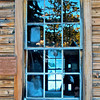 Window in old, abandoned wood-frame firehouse, Johnsville, CA (Plumas County). Dedication plaque is to left.  [UFP0010911]