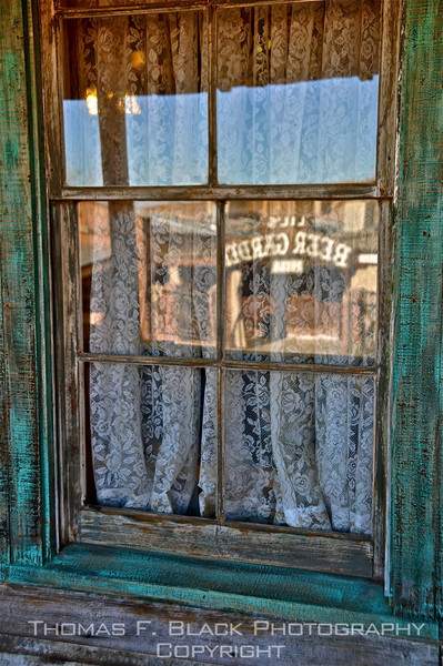 "Calico Ghost Town, Draggett, CA. Refection in pane reads ""Beer Garden,"" saloon across street.  [UFP070310]"