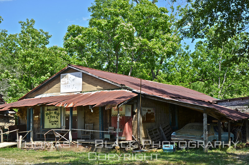This frame and next, outbuilding at Sciple's Water Mill, MS. Car is mid-1960s Chevrolet Chevelle. Note old Coca Cola vending machine (drinks last sold for 75 cents a bottle). [UFP050611]