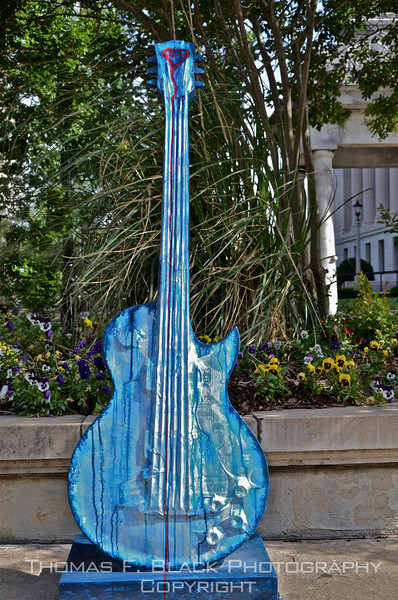 One of several large commissioned sculptures lining main drag of El Dorado, AR. Guitar stands a good 10 feet tall. Building in background is county courthouse. [UFP050511]