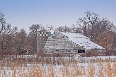 Abandoned barn and silo hiding in a grove of trees in southern North Dakota. Enjoy and hold hands.