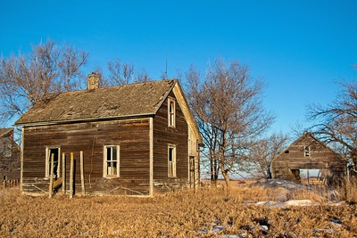 Abandoned farmstead in central South Dakota. The farmhouse is the smallest structure on the farm. The barn in the background is really large. Enjoy and hold hands.