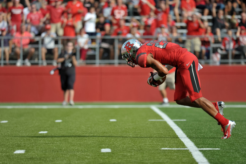 Rutgers' BRANDON JONES scoops up a block punt and runs toward the end zone.
