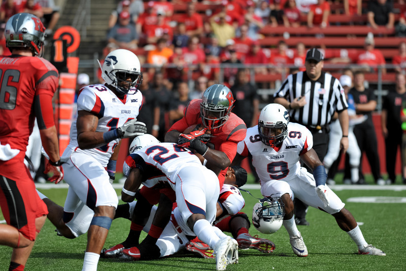 Rutgers' running back, SAVON HUGGINS, carries the ball for a short gain against the Howard University defense.