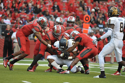 Six Rutgers defenders attempt to take down Kent State runningback, TRAYION DURHAM (34), who rushed for 131 yards in the game.