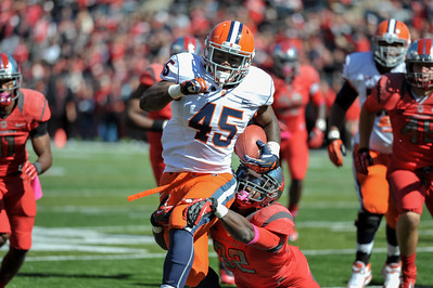 Syracuse running back, JEROME SMITH (45), tries to break free of Rutgers defensive back, DURON HARMON (32).