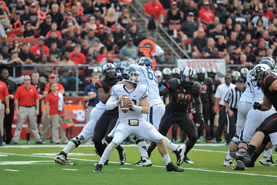UConn quarterback, CHANDLER WHITMER (10), looks to pass downfield against the Rutgers University defense.