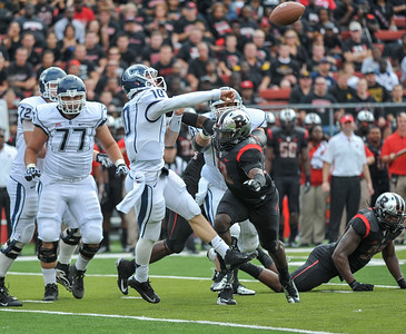 UConn quarterback, CHANDLER WHITMER (10), looks to pass downfield as Rutgers' KA'LIL GLAUD (13) pursues him.