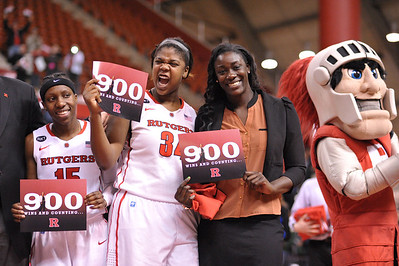 Rutgers forwards, MONIQUE OLIVER and CHELSEY LEE, celebrate head coach, C. VIVIAN STRINGER's 900th career victory after Rutgers defeated South Florida in a game at the Rutgers Athletic Center in Piscataway, New Jersey.