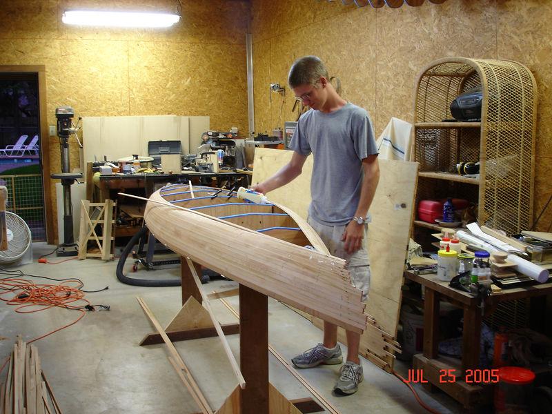 Woodshop with Ryan gluing cedar strips on the kayak.