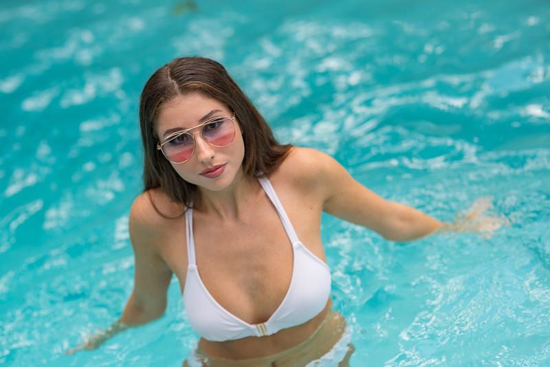 Beautiful young woman posing in a bikini with sunglasses