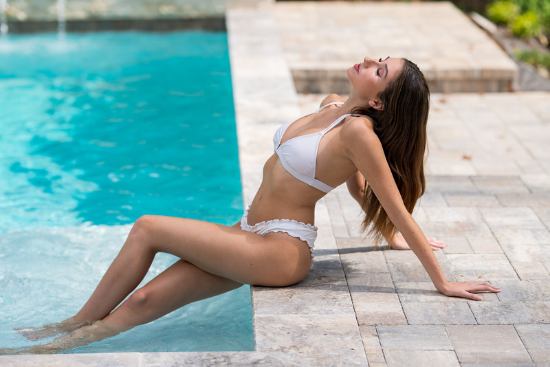 Photo of a young bikini model posiung by the pool. Summer vacation theme and healthy lifestyles