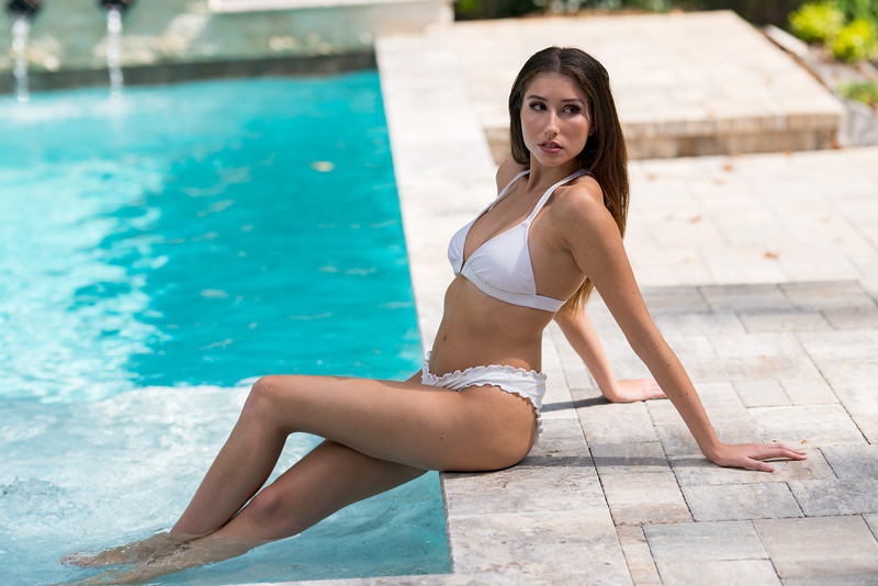 Attractive young lady posing by the pool with feet in the water