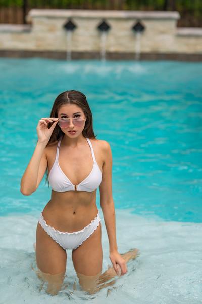 Woman posing in a bikini on her knees in a shallow pool