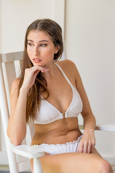 Sexy young woman sitting in a bikini and hand under chin