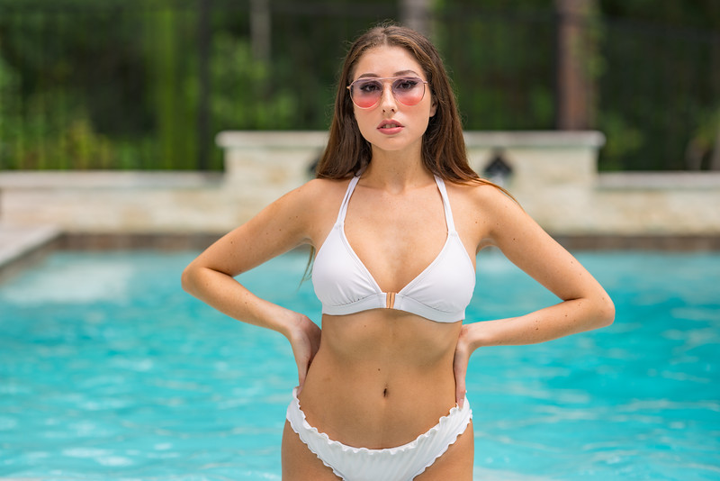 Beautiful woman posing in the pool with hands on hips