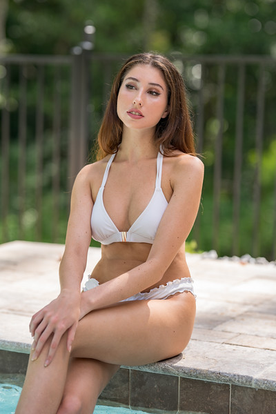 Attractive young woman healthy outdoor lifestyles sitting by the pool glancing away from camera