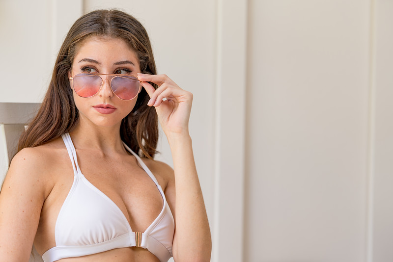 Beautiful woman sitting in a bikini and removing sunglasses to get a better look
