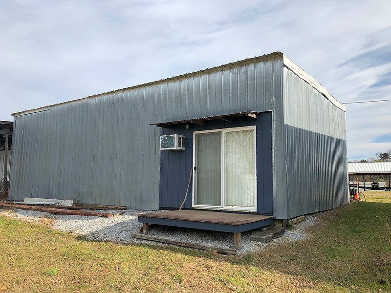 Back of hangar with sliding doors and deck.