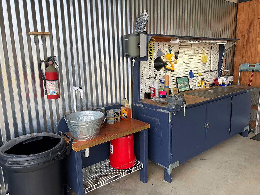 Sink that drains outside of hangar. Heavy duty workbench with LED Light.