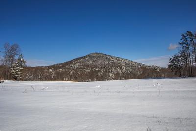 Snowy field looking at Flat Shoals Mountain near Danbury, NC, followng 9+ inches of snow.