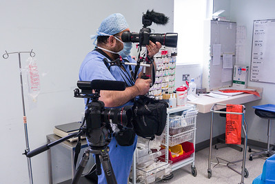 Photographer and film maker Edmond Terakopian filming at the Royal National Orthopaedic Hospital in Stanmore.  Filming in an operating theatre with two Canon 5D MkII camera, one on a Gitzo (GT3531LSV + G1380 head) and the other on a Zacuto Striker with the Zacuto Z-Finder Pro attached). Both cameras have Rode microphones attached for ambient sound recording. The VideoMic (closer) and VideoMic Pro. A Think Tank Photo Multimedia Wired Up 10 belt pack is also being used. May 16, 2011. Photo: Neil Patience