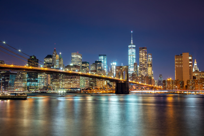 58149535 - new york -  view of manhattan skyline with skyscrapers  and famous brooklin bridge by night and city illumination, usa