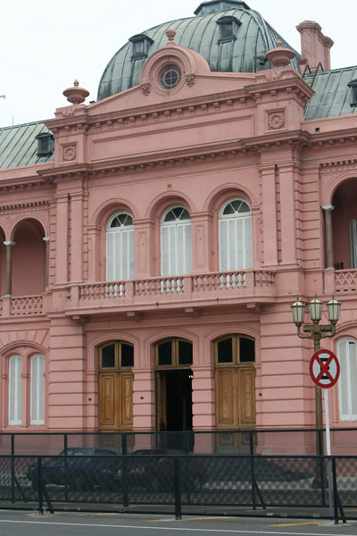 """La Casa Rosada is the executive mansion and office of the President of Argentina. The palatial mansion is known officially as Casa de Gobierno, which means """"House of Government"""" or """"Government House"""" in English language.  The characteristic color of the Casa Rosada is baby pink, and is considered one of the most emblematic buildings in Buenos Aires. It also has a museum, which contains objects relating to former presidents of Argentina and is a National Historic Monument of Argentina."""