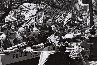 """FLAG WEAVING NEW YORKERS WATCHING THE OFFICIAL    WELCOME CEREMONY FOR P.M. LEVY ESHKOL OUTSIDE NEW YORK      CITY HALL.  áé÷åø øàù äîîùìä ìåé àùëåì áàøä""""á.  áöéìåí, î÷áìé ôðéí îðåôôéí áãâìéí            áè÷ñ ÷áìú ôðéí ìøàù äîîùìä áðéå éåø÷."""