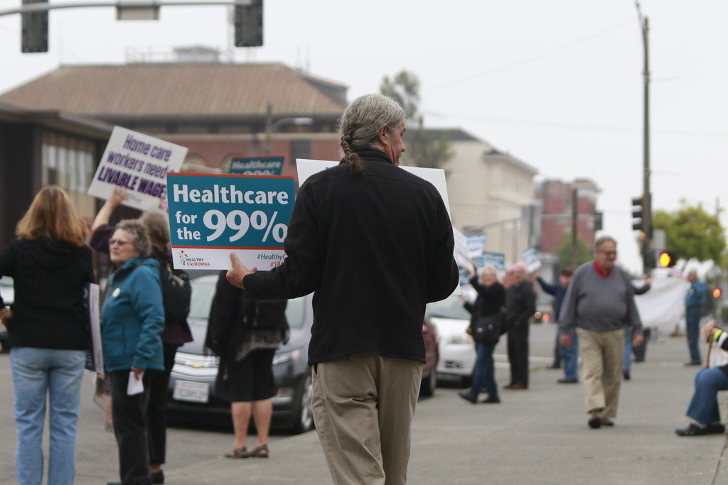 . Steve Madrone holding up signs to traffic during a rally in support of SB 562 outside of the Humboldt County Courthouse in Eureka on Monday morning.  (Hunter Cresswell - The Times-Standard)