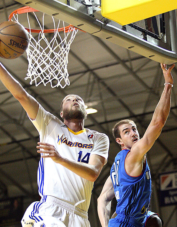 . Santa Cruz Warriors forward Scott Wood slips underneath the basket to score in front of Oklahoma City defender Alex Caruso during the first game of their D-League playoff match Wednesday night.  (Dan Coyro -- Santa Cruz Sentinel)