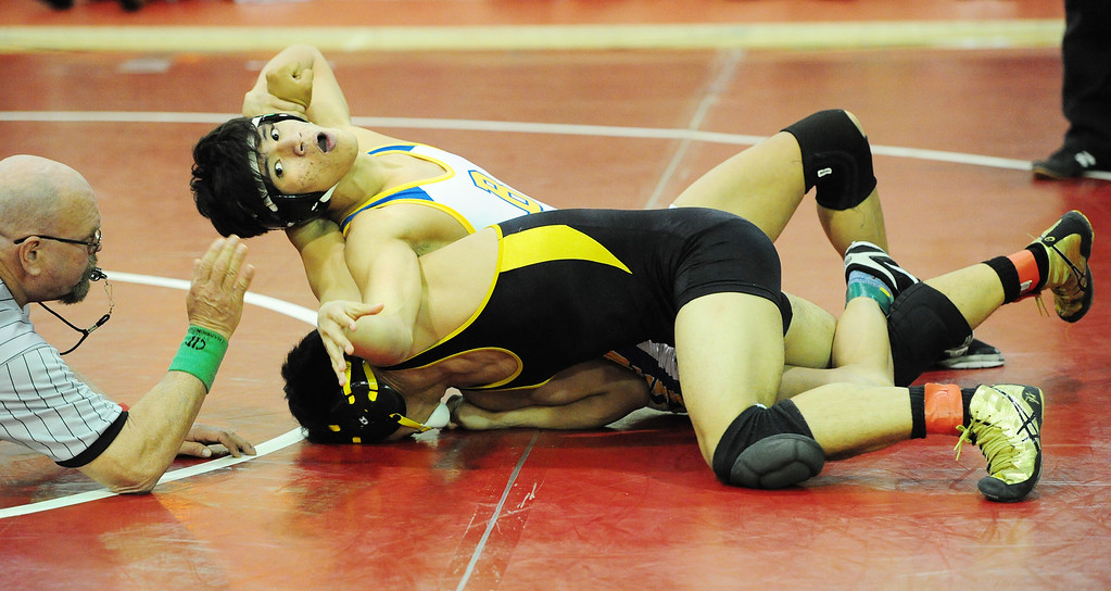 . (CHRIS RILEY �TIMES-HERALD) Benicia\'s Justin Gomez wrenches the arm of Anthony Bonifacio from Jesse Bethel during their 152 pound match at the Solano County Athletic Conference finals in Vallejo on Friday.