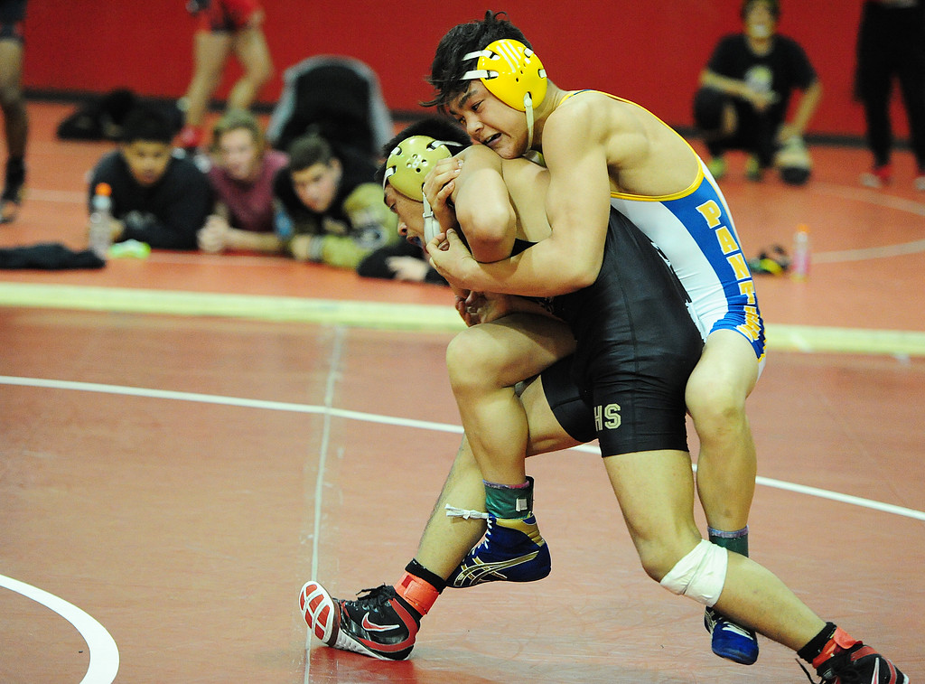 . (CHRIS RILEY �TIMES-HERALD) Benicia\'s Basil Othman holds on to American Canyon\'s Aaron Villas Carlos during their 126 pound match at the Solano County Athletic Conference finals in Vallejo on Friday.