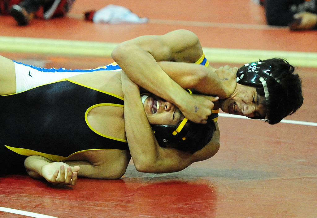 . (CHRIS RILEY �TIMES-HERALD) Benicia\'s Justin Gomez squeezes Anthony Bonifacio from Jesse Bethel during their 152 pound match at the Solano County Athletic Conference finals in Vallejo on Friday.