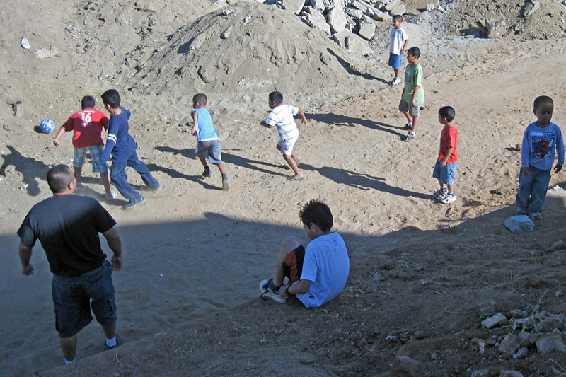 Rodrigo (left) & boys play soccer near the dump