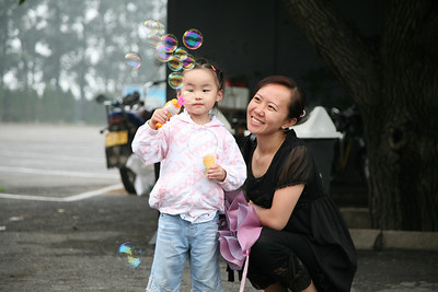 Girl and Mom blowing bubbles outside of the Ming Tombs